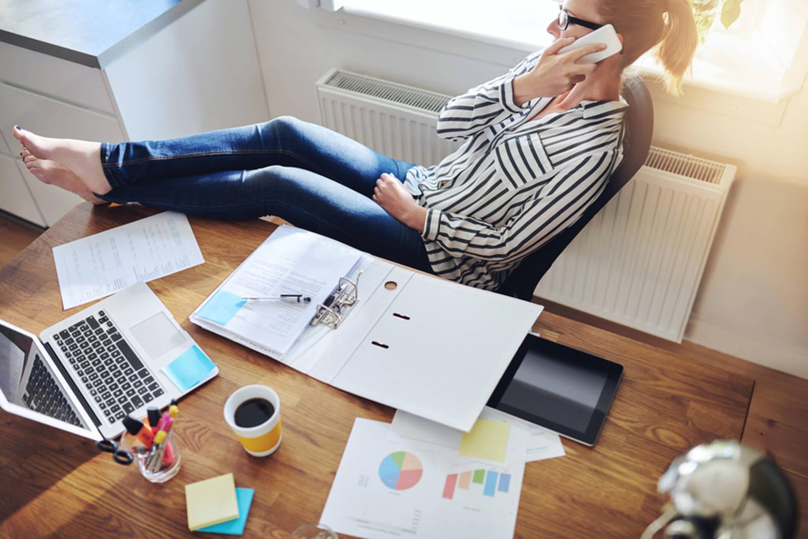 Ein Frau hat ihre Füsse auf ihrem Arbeitstisch während sie einen Telefonanruf erledigt.
