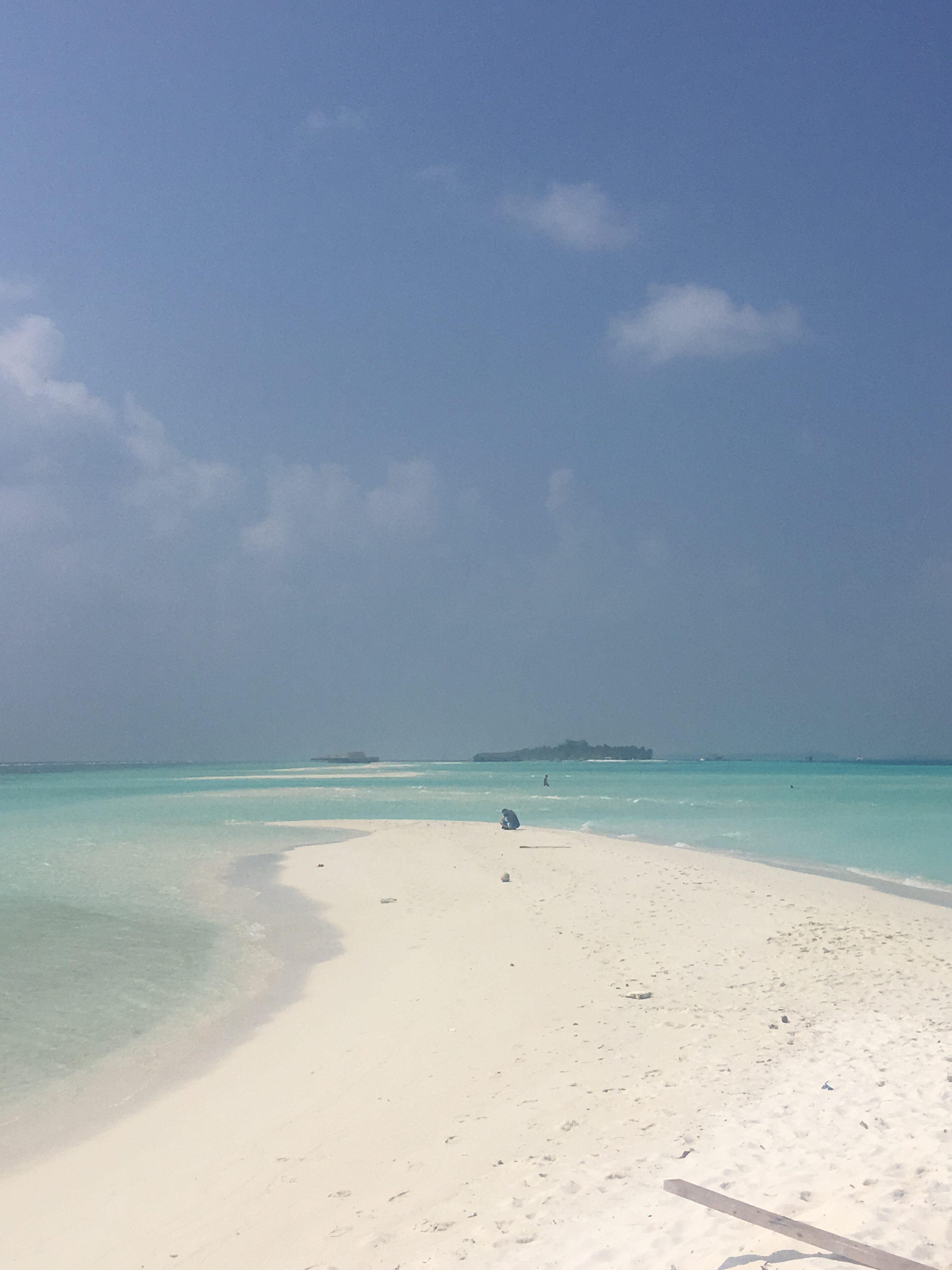 Eine schmale Sandbank führt ins türkise Meer hinaus.