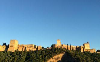 Eine Festung thront auf einem Hügel Granadas. Die Alhambra im Abendlicht.