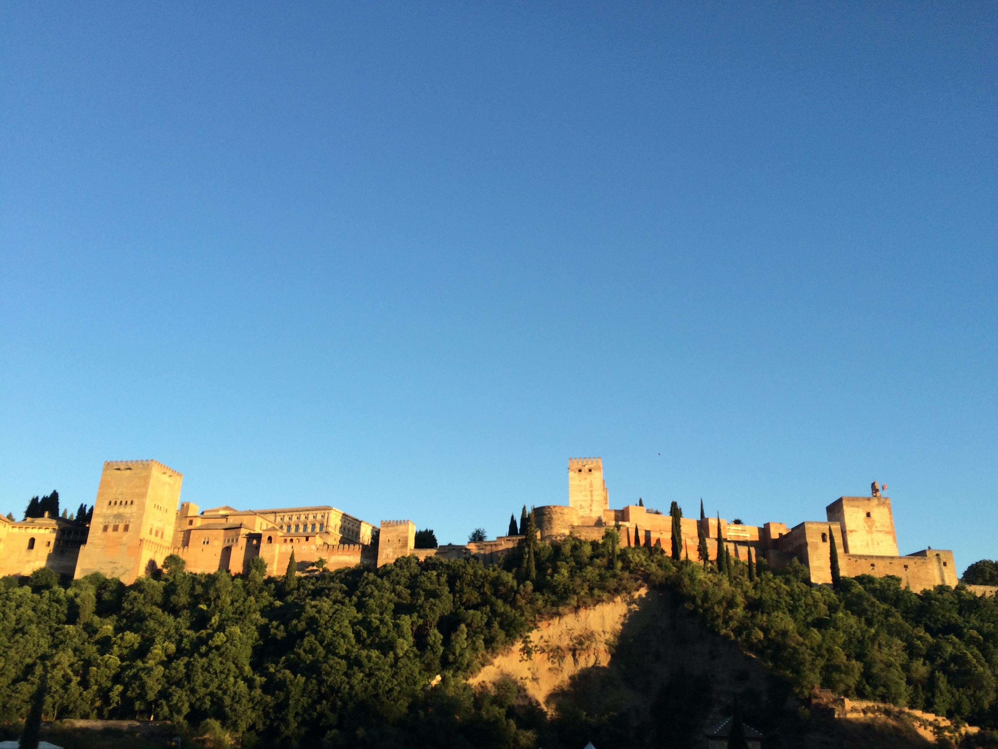 Die Festung Alhambra im Abendlicht auf einem Hügel über der Stadt Granada.
