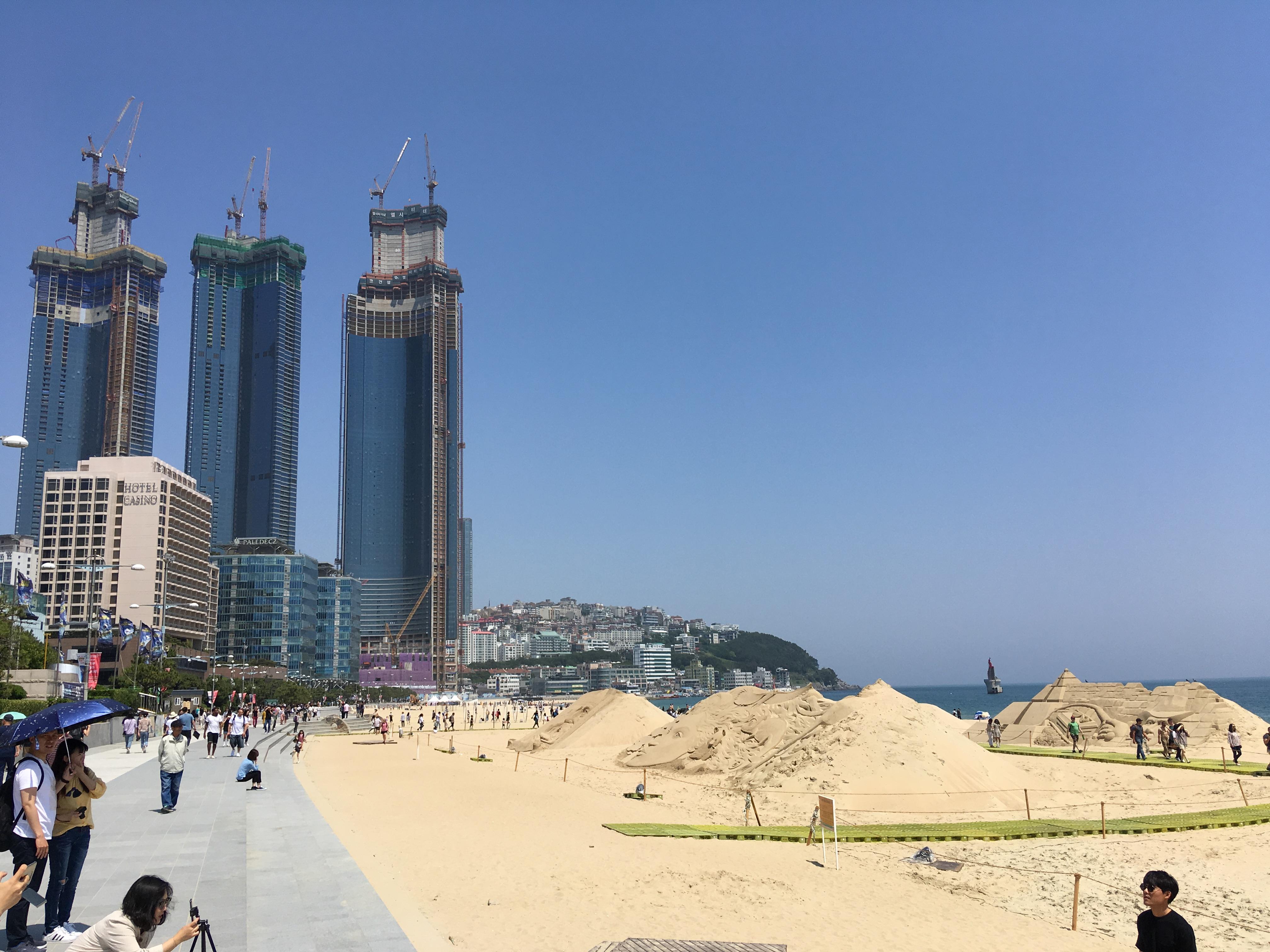 Ein Strandabschnitt mit Sandschlössern ist zu sehen. Dahinter Wolkenkratzer.