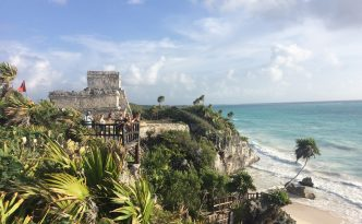 Auf diesem Bild ist eine wunderschöne Maya Ruine in Mexico, genauer gesagt in Tulum zu sehen. Vor den Ruinen sind Palmen zusehen und gleich darunter ein weisser Strand.
