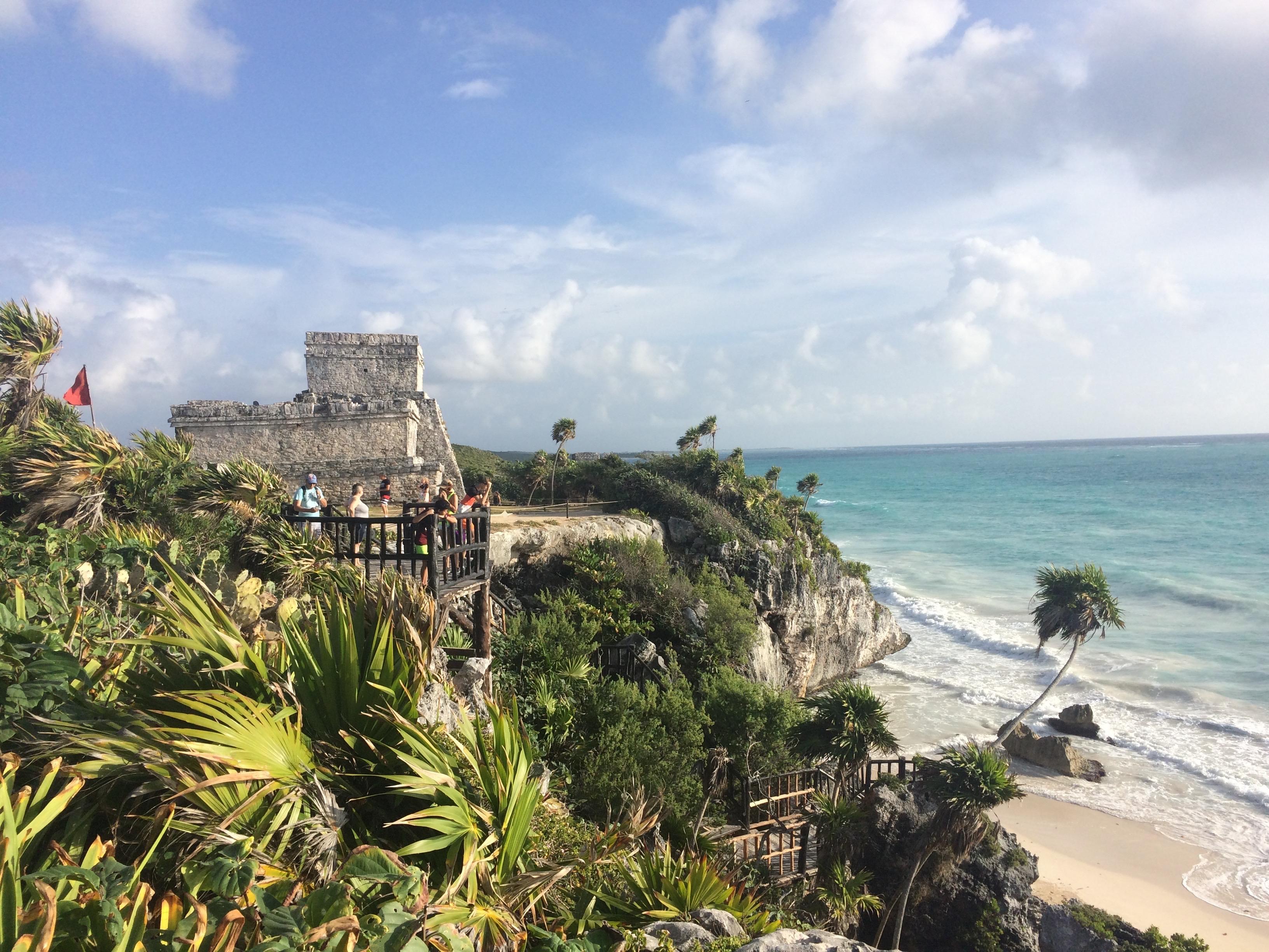 Über einer kleinen Bucht mit Strand thront ein Maya Ruine, die von Palmen umgeben ist.