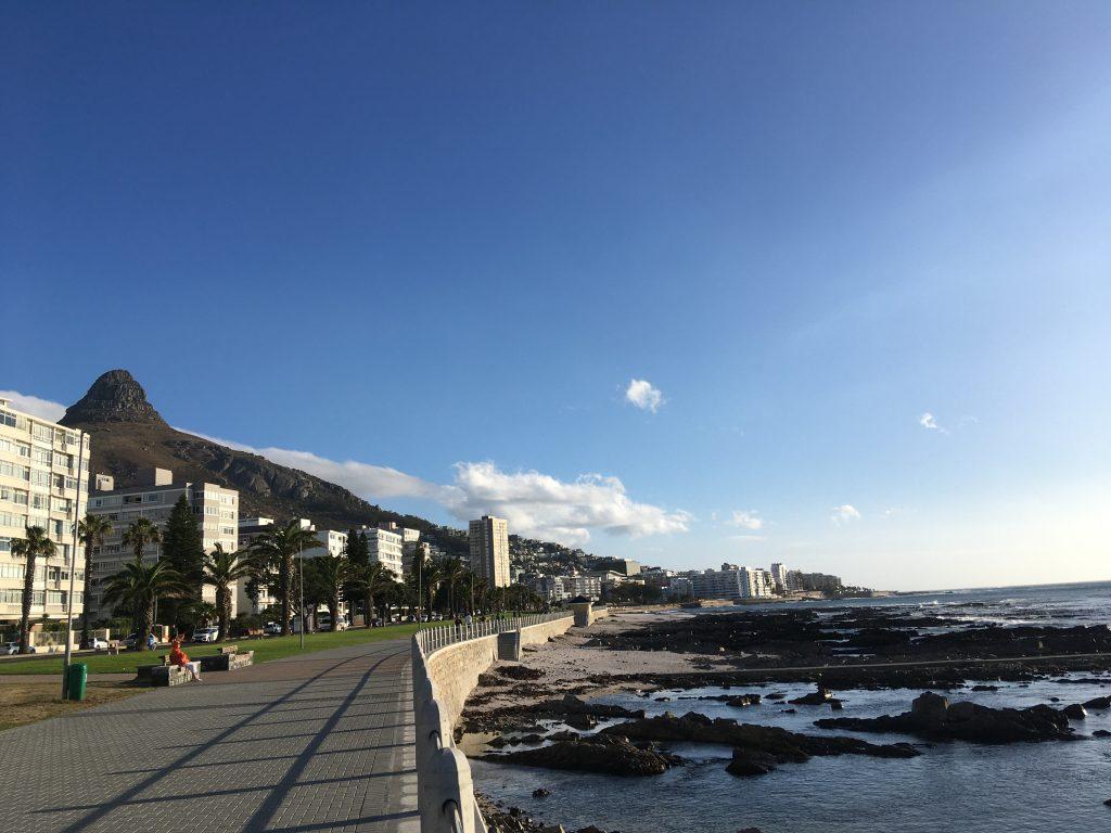 Das Bild zeigt eine lange Meerpromenade, Häuser und einen spitzen Berg im Hintergrund, den Lions Head in Kapstadt.